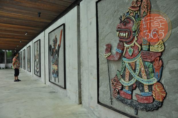 在走廊上欣赏刻画的皮影戏画
